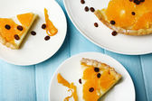 Piece of homemade orange tart on plate, on color wooden background — Stock Photo