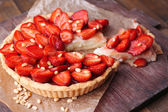 Strawberry tart on wooden tray, on rustic wooden background — Stock Photo