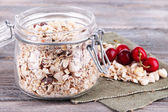 Homemade granola in glass jar, on color wooden background — Stock Photo