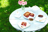 Coffee table with teacups and tasty pie in garden — Foto de Stock