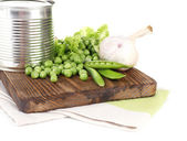 Fresh peas and tin on wooden board, isolated on white — Stock Photo