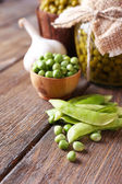 Fresh  and canned peas in bowl and glass jar on napkin, on wooden background — Stock Photo