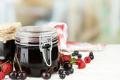 Tasty jam with berries in glass jars on wooden table — Stock Photo