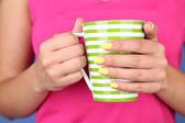 Woman with stylish colorful nails holding mug, close-up, on color background — Foto Stock