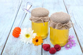 Jar full of delicious fresh honey and wild flowers on wooden table — Stock Photo