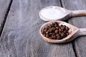 盐和胡椒在勺子上木桌特写 — 图库照片