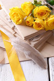 Old letters and flowers on wooden background close-up — Stock Photo