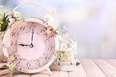 Beautiful vintage alarm clock with flowers on light background — Foto de Stock