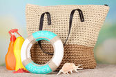 Summer wicker bag with accessories on sand, on nature background — Stock Photo