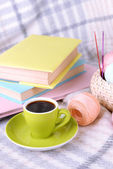 Cup of coffee and yarn for knitting on plaid with books close-up — Stock Photo
