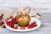 Sweet caramel apple on stick with berries, on wooden table — Stock Photo