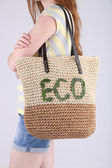 Woman with summer wicker Eco bag, on grey wall background — Stock Photo