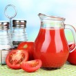 Tomato juice in glass jug, on wooden  table, on bright background — Stock Photo #49347523