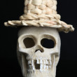 Skull in funny wicker hat isolated on black — Stock Photo #49348005