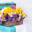 Beautiful flowers in crate on small chair on light background — Stock Photo #49348873