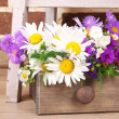 Beautiful flowers in crate on small ladder on brick wall background — Stock Photo #49348913