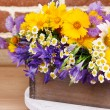 Beautiful flowers in crate on brick wall background — Stock Photo #49348915