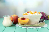 Sour cheese and pieces of fresh peach,on wooden table, on light  background — Stock Photo
