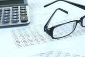 Calculator and glasses with documents close up — Stock Photo