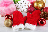 Red winter mittens with Christmas toys on wooden table — Stock Photo