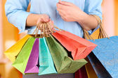 Young woman holding colorful shopping bags in  her hand, on bright background — Stock Photo