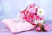 Beautiful wedding bouquet and cushion with rings on table on bright background — Stock Photo