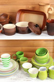 Different tableware on shelf, on wooden background — Stok fotoğraf