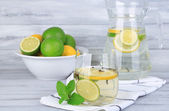 Fresh summer drink with lime and cloves in glass and jug, on color wooden background — Stockfoto