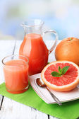 Half of grapefruit, glass jug with fresh juice and spoon on plate on light background — Stock Photo