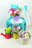 Bouquet of colorful flowers in decorative buckets, on chair, on home interior background — Stock Photo