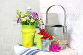 Bouquet of colorful flowers and fresh cherries in decorative buckets, on chair, on light wall background — Stock Photo