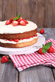 Delicious biscuit cake with strawberries on table on wooden background — Stock Photo