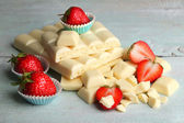 White chocolate bar with fresh strawberries, on color wooden background — Stock Photo