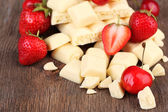 Broken white chocolate bar with fresh strawberries, on color wooden background — Stock Photo