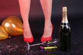 Legs with confetti, champagne and balloons on the floor — Stock Photo
