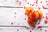 Tasty muffin with red currant berries on color wooden background — Stok fotoğraf