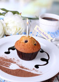 Blueberry muffin with chocolate sauce on plate, on wooden table, on bright background — Stock Photo