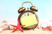 Summertime. Old clock on sand  — Stok fotoğraf