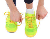 Young woman tying shoelace isolated on white — Stock Photo