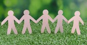 Paper people on green grass, close up — Stock Photo