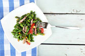 Salad with green beans, ham and  corn on plate, on color wooden background — Stock Photo