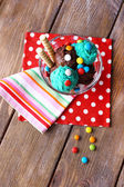 Chocolate ice cream with multicolor candies and wafer rolls in glass bowl, on wooden background — Stok fotoğraf