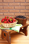 Fresh berries in baskets on wall background — Stock Photo