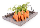 Fresh carrot with leaves on wooden tray isolated on white — Stock Photo