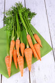 Fresh carrot on napkin on wooden background — Stock Photo