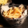 Tasty french fries in metal basket and potato chips on wooden table with dark light — Stock Photo