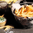 Tasty french fries in metal basket and potato chips on wooden table with dark light — Stock Photo #49350159