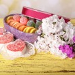 Present box with sweets and flowers on table on bright background — Stock Photo #49350341