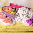 Present box with sweets and flowers on table on bright background — Stock Photo
