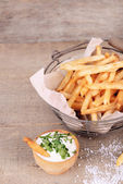 Tasty french fries in metal basket on wooden table — Stock Photo